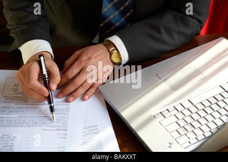 Homme assis à côté de l'écriture de l'ordinateur sur un document Banque D'Images