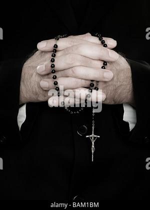Un gros plan du prêtre holding prayer beads Banque D'Images