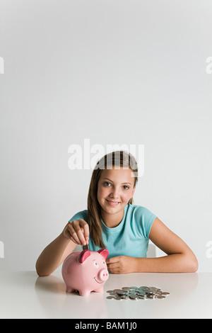 Girl with piggy bank et pièces Banque D'Images