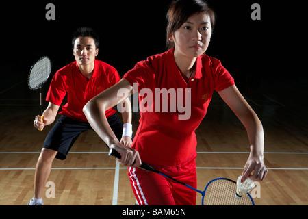 Jeune homme et femme la préparation au retour d'un tir de Badminton Banque D'Images