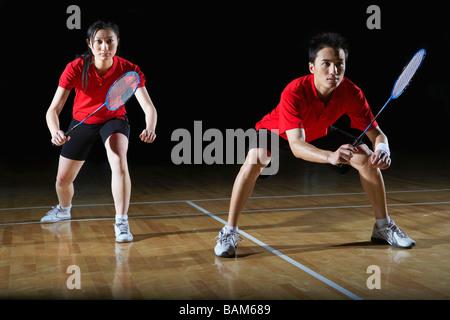 L'homme et la femme en action jouer au badminton Banque D'Images