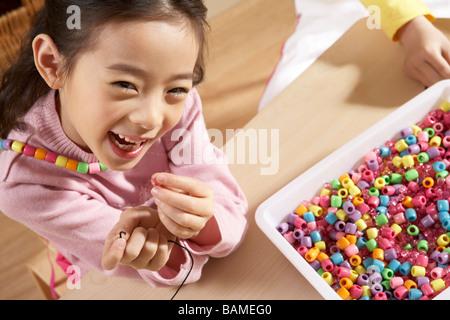 Fille de rire et jouer en classe avec des perles Banque D'Images