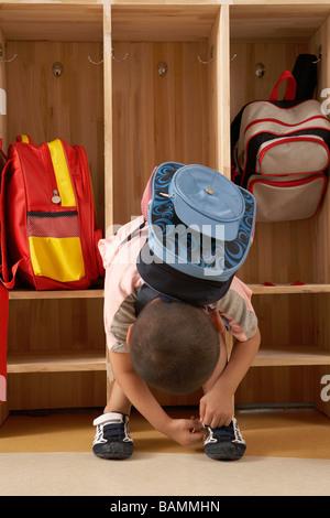 Jeune garçon attacher ses lacets dans un vestiaire Banque D'Images