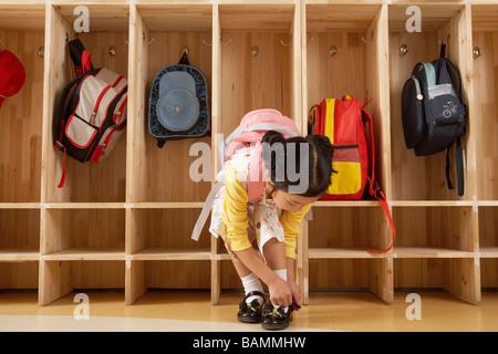Jeune fille lier ses lacets dans un vestiaire Banque D'Images