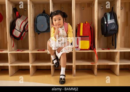 Jeune fille assise dans un vestiaire Banque D'Images
