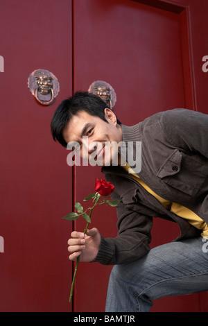 Jeune homme Porte d'attente amplexicaule une rose rouge Banque D'Images