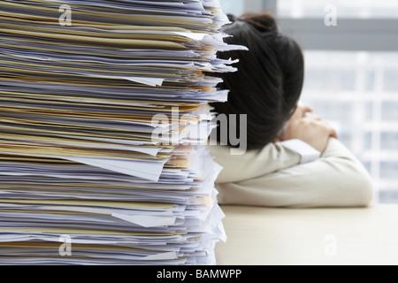Businesswoman Sleeping Next to Pile de travail Banque D'Images