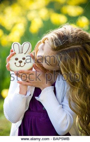 Une jeune fille tenant un lapin en chocolat, portant des oreilles de lapin Banque D'Images