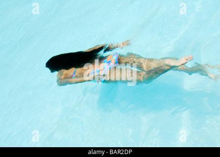 Girl swimming underwater de longs cheveux noirs piscine Banque D'Images