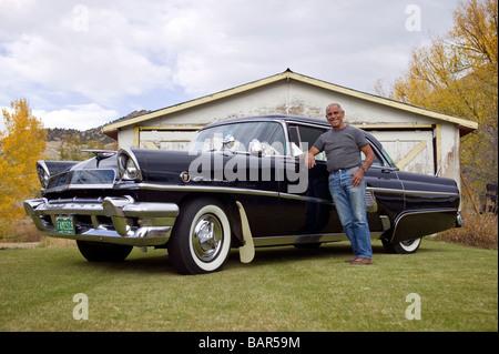 Portrait d'un homme âgé avec ses meubles anciens 1955 automobile de mercure à son domicile dans la petite ville Banque D'Images