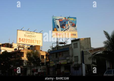 Des panneaux dans le coucher du soleil contre un ciel bleu avec des bâtiments sales et Street View ci-dessous à Banque D'Images