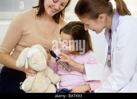 Médecin et l'enfant à jouer. Mère regardant tandis que sa fille et d'un médecin jouer avec un otoscope. Banque D'Images