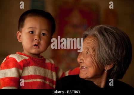 Changchun, Jilin, Chine. Un jeune garçon dans les bras de sa grand-mère dans leur petite maison. Banque D'Images