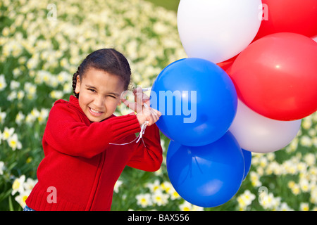 Une belle jeune mixed race girl Playing with balloons dans un champ de jonquilles Banque D'Images