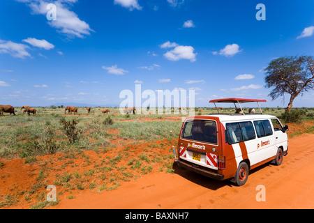 Un bus de touristes en safari regarder famille de brousse africaine éléphants dans la savane, le parc national de Banque D'Images