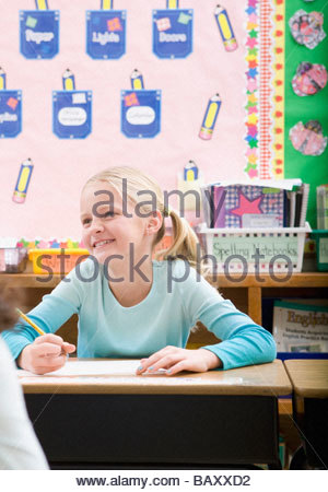 Student writing at desk in classroom Banque D'Images