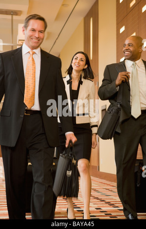 Multi-ethnic business people walking down corridor avec des valises Banque D'Images