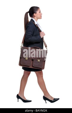 Businesswoman walking with briefcase par dessus son épaule isolé sur fond blanc Banque D'Images