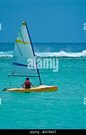 Man sailing dans un voilier jaune sur l'Océan Indien près de la plage à l'Ile Maurice, horizontal Banque D'Images