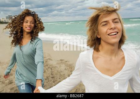 Teenage boy holding main d'une fille sur la plage Banque D'Images