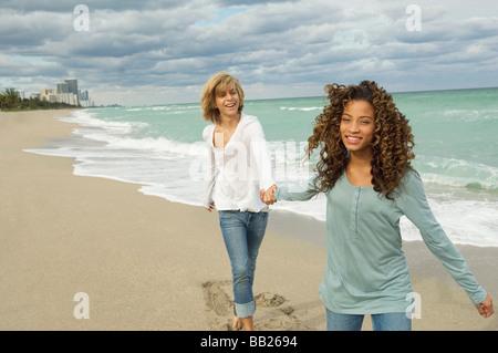 Girl holding hand of a Teenage boy sur la plage Banque D'Images
