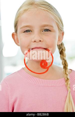 Portrait of a Girl holding a candy dans sa bouche Banque D'Images