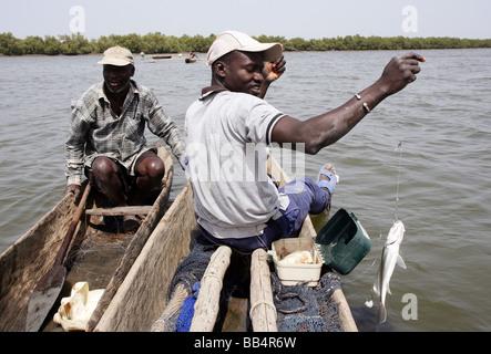 Sénégal: les pêcheurs de sa pirogue sur le fleuve Casamance Banque D'Images