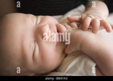 Bébé nouveau-né garçon avec les mains sur son visage, à la recherche d'un moyen de sucer son pouce Banque D'Images