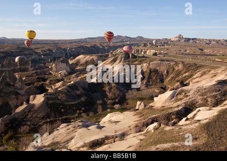 Montgolfières dans un vol tôt le matin sur le terrain accidenté de la Cappadoce Turquie Banque D'Images
