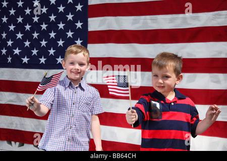 Deux jeunes garçons brandissant des drapeaux américains Banque D'Images
