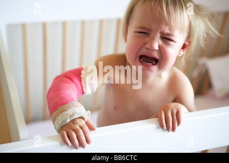 Pleurer tout-petit avec le bras dans le plâtre Banque D'Images