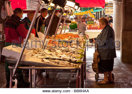 Femme d'acheter du poisson au marché aux poissons du Rialto à Venise Banque D'Images