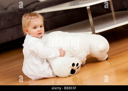Jeune fille, 1 ans, jouant sur le plancher avec un jouet ours polaire Banque D'Images