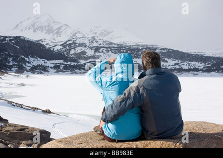 Couple assis en face de la montagne de neige et de glace Banque D'Images