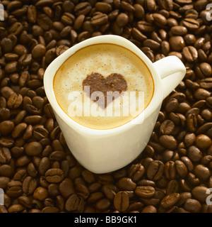 Une tasse de café cappuccino style avec une forme de coeur sur le dessus, tourné sur les grains de café. Banque D'Images