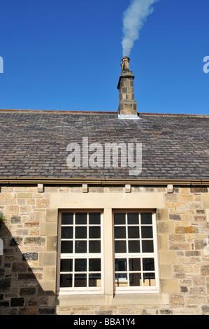 Ancienne cheminée sur toit de tuiles avec fond de ciel bleu Banque D'Images