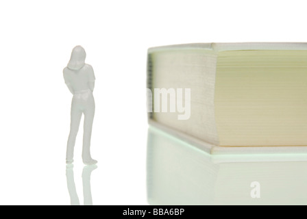 La figure d'une femme miniature avec curiosité debout en face d'un livre, image symbolique de la connaissance Banque D'Images