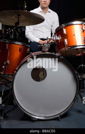 Un homme assis à un kit de batterie Banque D'Images