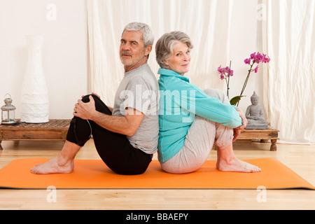 Droit assis dos à dos sur un tapis d'exercice Banque D'Images