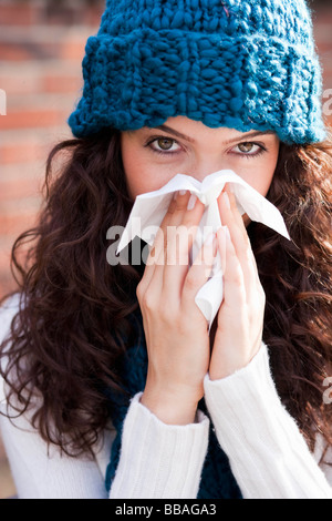 Young woman wiping nose Banque D'Images
