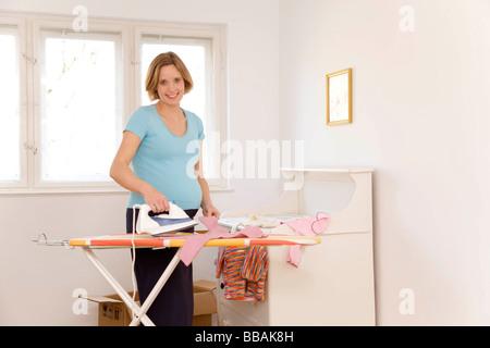 Repassage femme enceinte vêtements de bébé Banque D'Images