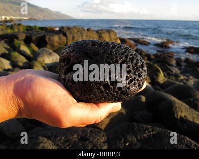 Main tenant la pierre de lave, sur la côte à La Palma, Îles Canaries, Espagne Banque D'Images