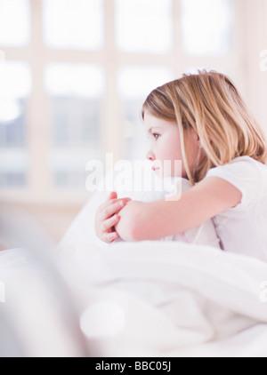 Fille au lit en regardant par la fenêtre Banque D'Images