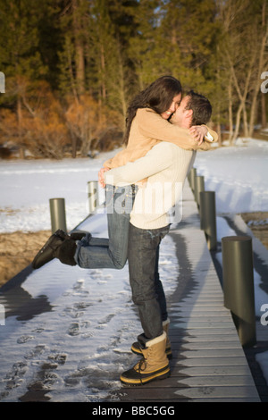 Homme Femme ramasser on snowy pier Banque D'Images