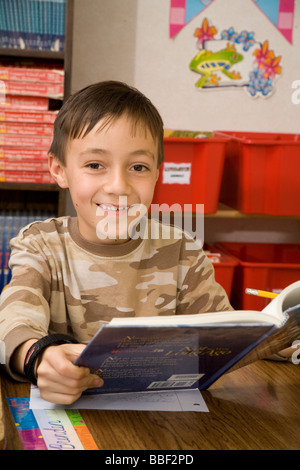 Portrait jeune garçon enfant enfants 8-10 ans Livre de lecture en classe à la 3ème année d'appareil photo smiling Banque D'Images