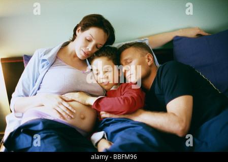 Famille ensemble au lit, garçon de placer la main sur l'estomac de la femme enceinte Banque D'Images