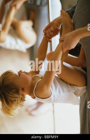 Little girl holding mother's hands, tournant flip contre son ventre Banque D'Images