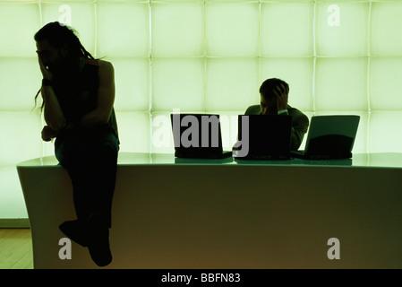 L'homme avec des dreadlocks assis sur 24, la main sous le menton, businessman using laptop computer Banque D'Images
