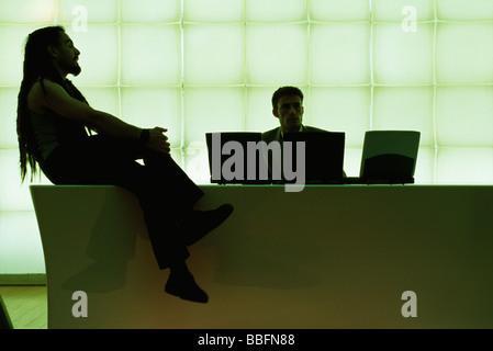L'homme avec des dreadlocks assis sur un bureau avec les jambes croisées, parlant de businessman using laptop computer Banque D'Images