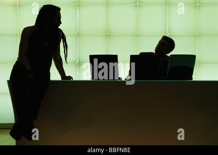 Avec des dreadlocks Man sitting on desk parlant de businessman using laptop computer Banque D'Images